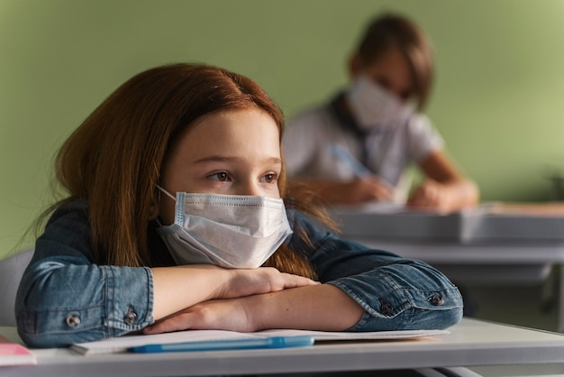 クラスで先生の話を聞いている医療用マスクを持った子供たち 無料写真