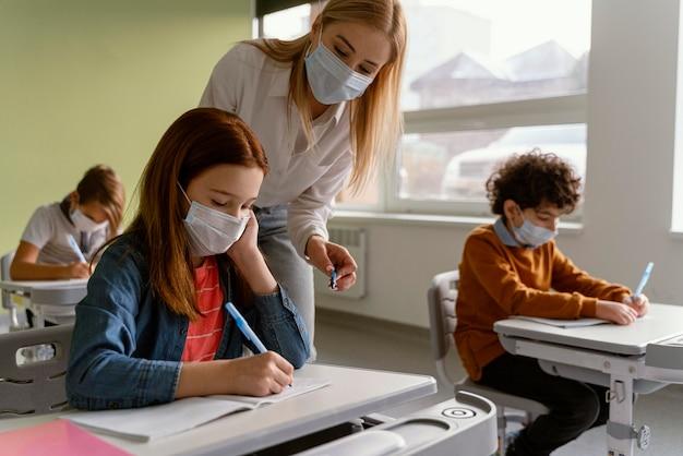 教師と一緒に学校で勉強している医療用マスクを持つ子供たち 無料写真