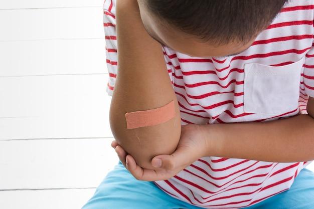 Children wound or the boy had an accident sitting on wooden white background. Premium Photo