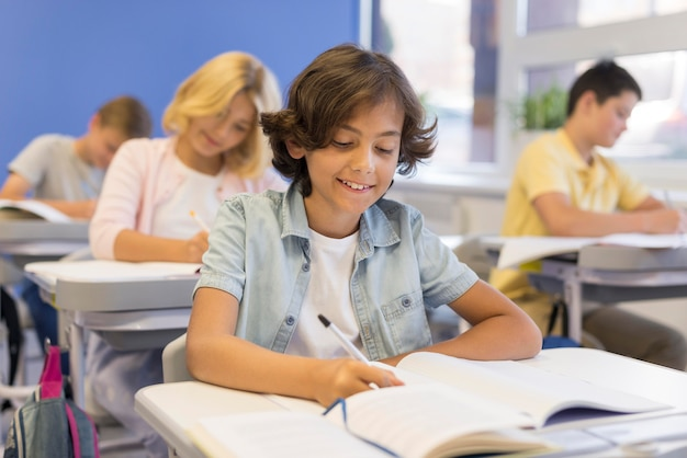 Childrens in classroom writing Free Photo