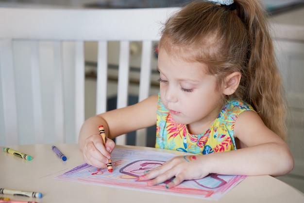 子供の創造性。子供の女の子が自宅でワックス鉛筆で描画します。世界的な検疫期間中のオンライン遠隔教育の概念。 Premium写真
