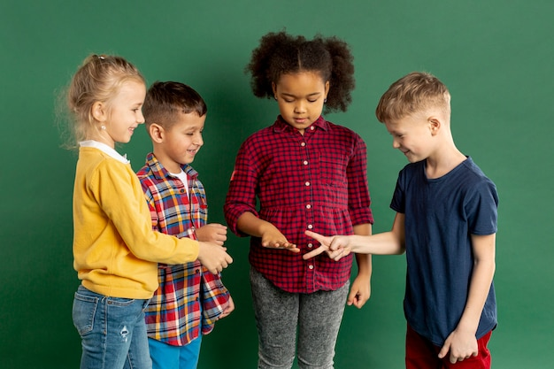 Childrens playing rock scissors paper game Free Photo