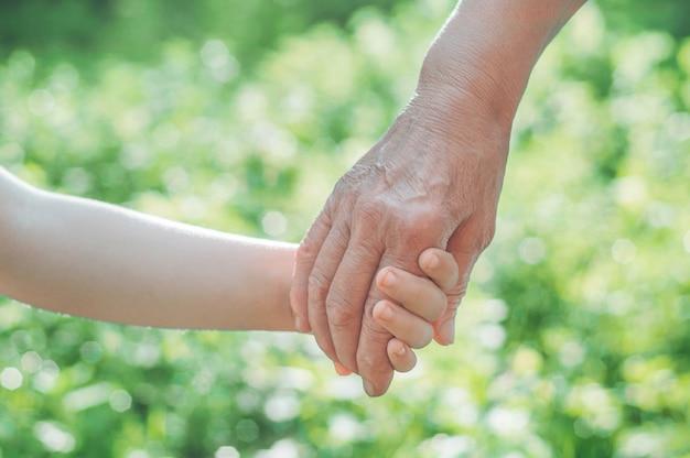 Чайлдс рука и старая бабушка Premium Фотографии