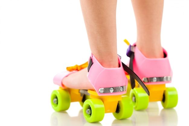 Чайлдс ноги в красочные смешные ролики на белом фоне Premium Фотографии