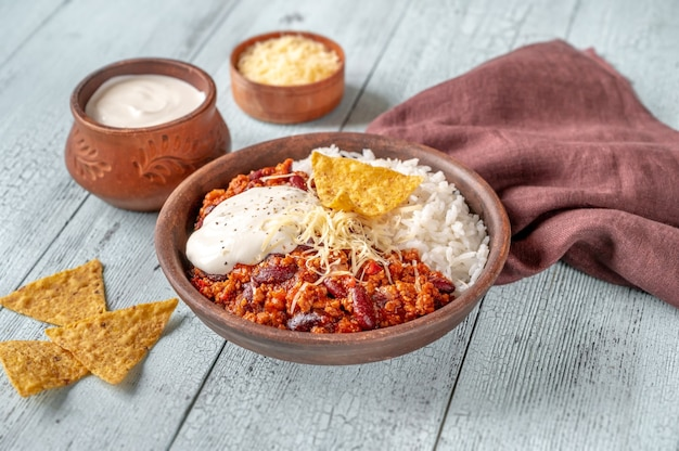 Chili con carne served with rice, grated cheese and tortilla chips Premium Photo