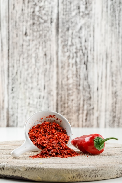 Chili powder with red pepper and wooden piece in a white scoop on white and wooden grunge wall, side view. Free Photo