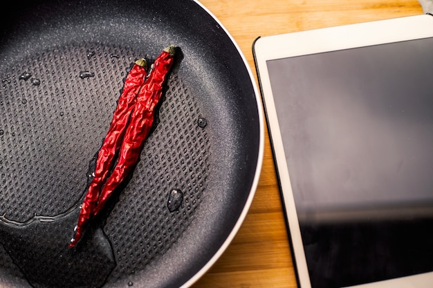 Chillies in a frying pan and tablet Free Photo