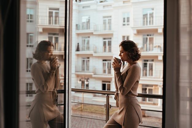 おいしいお茶のカップでポーズをとる身も凍るようなブルネットの少女。壮大な若い女性が窓の近くでコーヒーを飲む写真。 無料写真