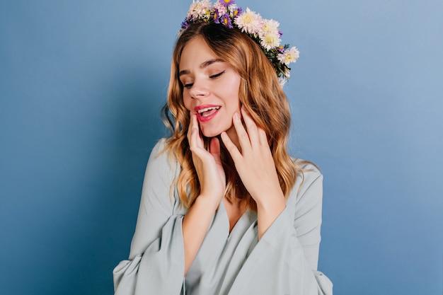 青い壁にポーズをとって花の花輪で身も凍るようなヨーロッパの女性 無料写真