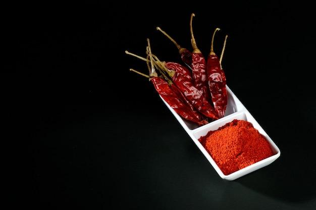 Холодный порошок с красным чили в белой тарелке, сушеный перец чили на черной поверхности Premium Фотографии