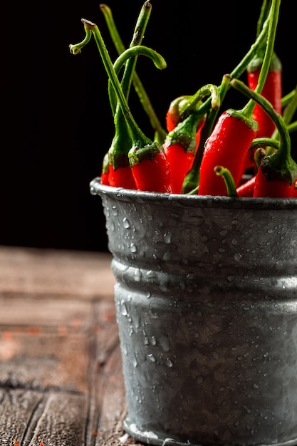 Chilly red peppers in a mini bucket close-up on stone tile and black Free Photo
