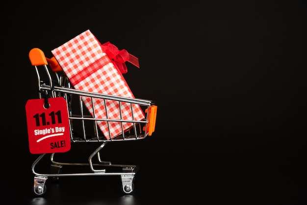 China, 11.11 single day sale, red ticket tag hanging on mini shopping cart with gift boxes Premium Photo