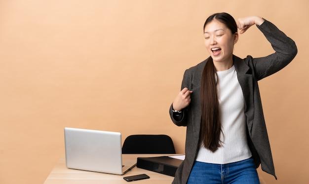 Китайская деловая женщина на своем рабочем месте, празднует победу Premium Фотографии