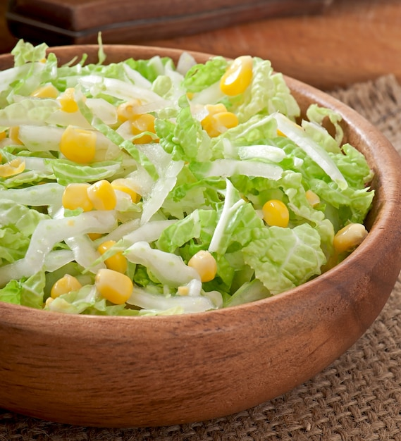 Chinese cabbage salad with sweet corn in a wooden bowl Free Photo