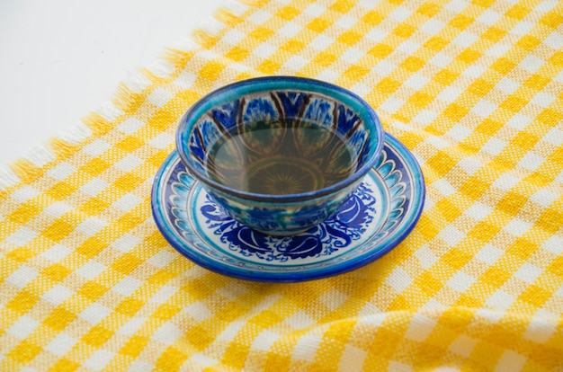 Chinese ceramics tea cup and saucer on yellow checkered table cloth Free Photo