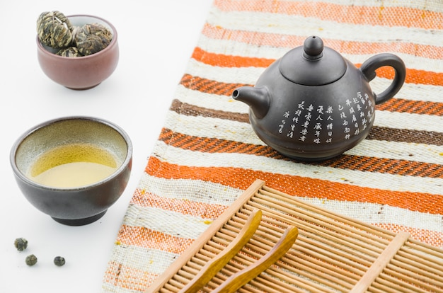 Chinese clay teapot with floral blooming tea ball tea cup against white backdrop Free Photo