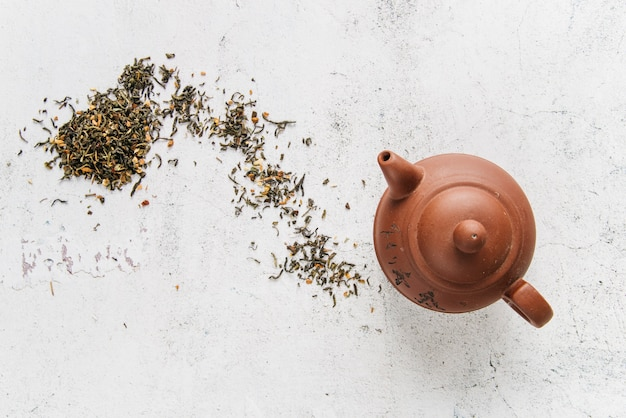 Chinese clay teapot with herbs on white concrete backdrop Free Photo