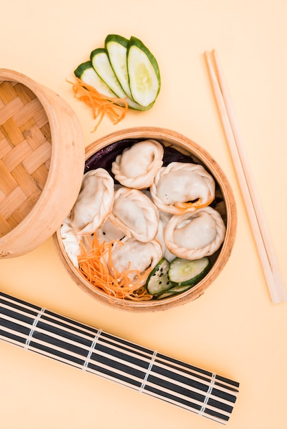 Chinese dumpling and salad in a bamboo steamer box on colored backdrop with chopsticks Free Photo