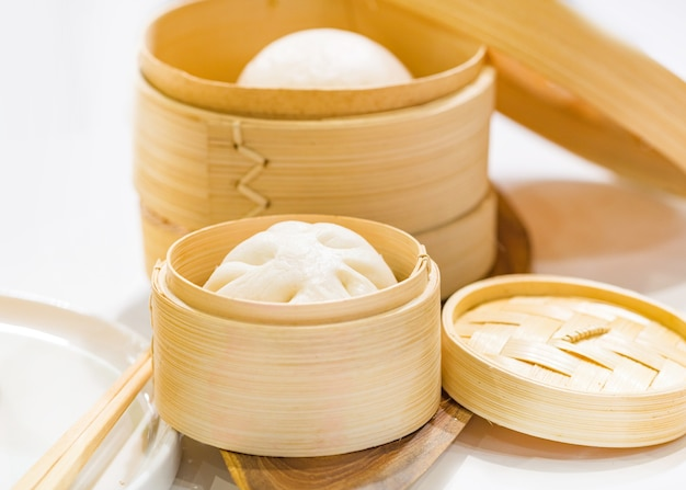 Chinese dumpling steamed buns, steamed bun served in wooden basket Premium Photo