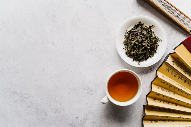 Chinese fan with herbal tea and dried leaves on concrete background Free Photo