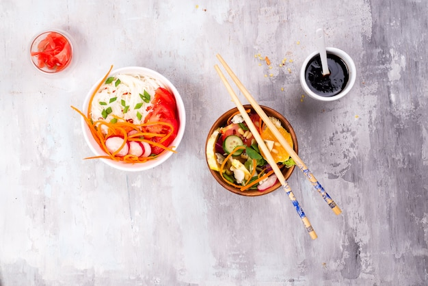 Chinese food salad, noodles with vegetables and nuts on gray stone background Premium Photo