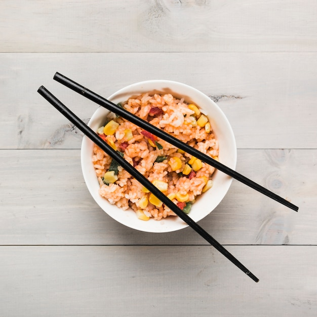 Chinese fried rice bowl with black chopsticks on wooden table Free Photo