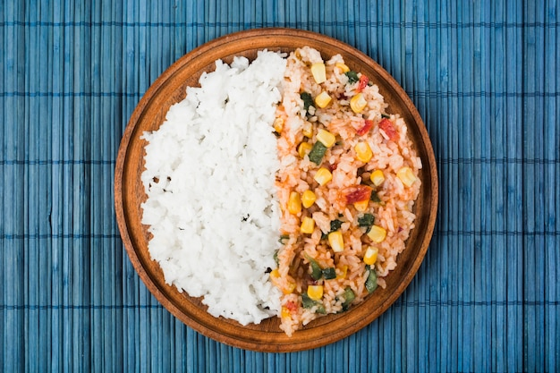 Chinese fried and steamed rice on wooden plate over the blue placemat Free Photo