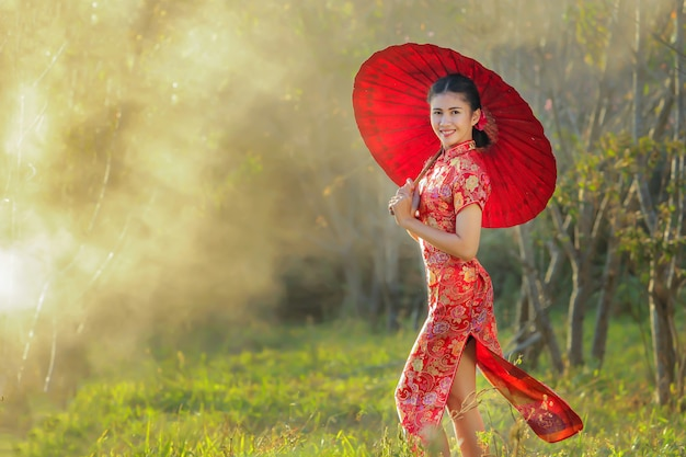 Chinese girl with dress traditional cheongsam in garden Premium Photo