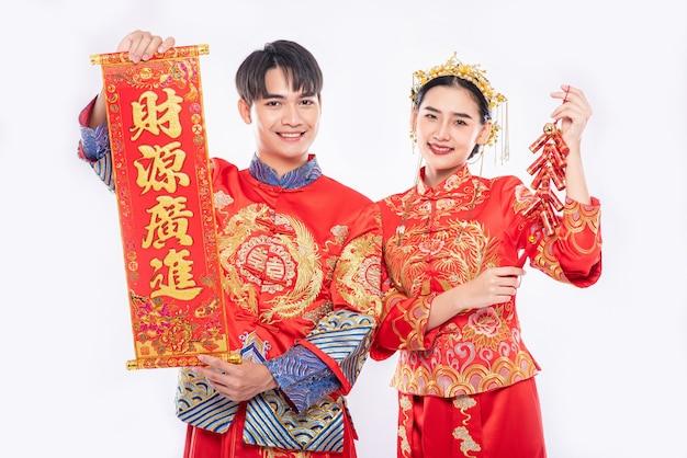 중국 인사 장과 폭죽은 중국 새해를 축하하기 위해 남자와 여자가 Cheongsam 정장을 입는 데 사용됩니다. 무료 사진