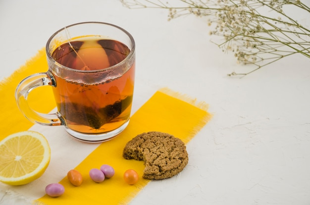 Chinese herbal tea cup with candies and eaten cookies on white background with gypsophila twig Free Photo