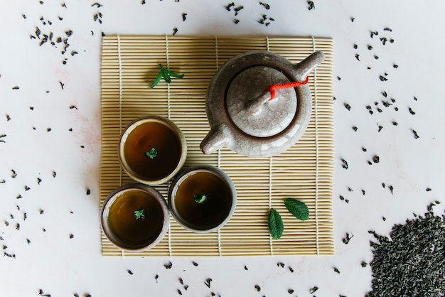Chinese or japanese traditional teapot; cup of tea on placemat Free Photo