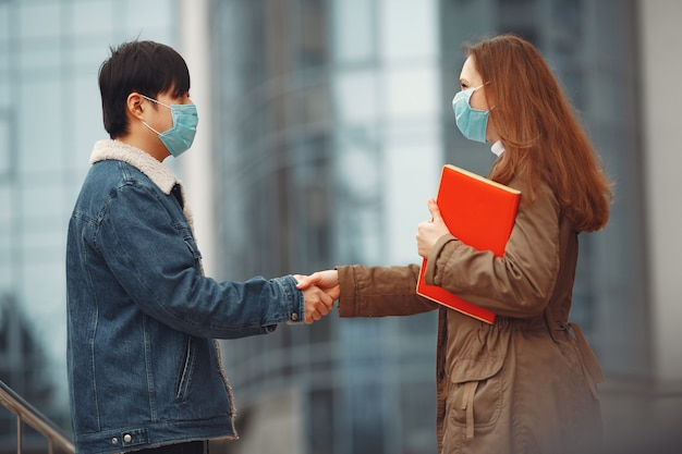 Chinese man and a woman in disposable masks  are shaking hands Free Photo