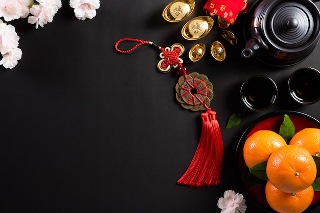 Chinese new year festival decorations pow or red packet, orange and gold ingots or golden lump on a black background. Premium Photo