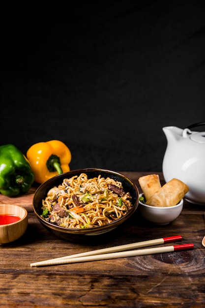 Chinese noodles with beef and vegetables served with spring rolls on wooden desk Free Photo