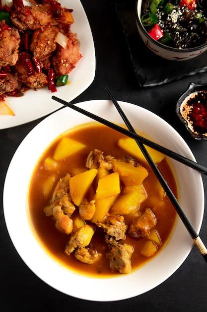 Китайский суп с курицей и картофелем в тарелке Бесплатные Фотографии