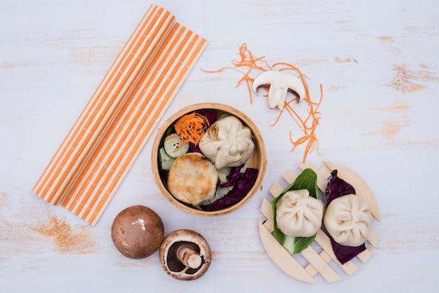 Chinese steamed dimsum in bamboo containers traditional cuisine on white wooden table Free Photo