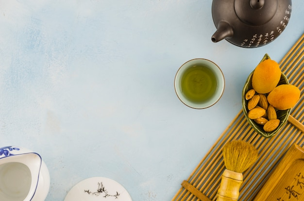 Chinese tea set with dried fruits and brush on white textured background Free Photo