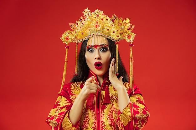 Donna graziosa tradizionale cinese allo studio sopra il rosso. Foto Gratuite