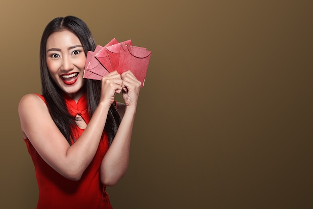 Chinese woman in tradional clothing holding angpao Premium Photo