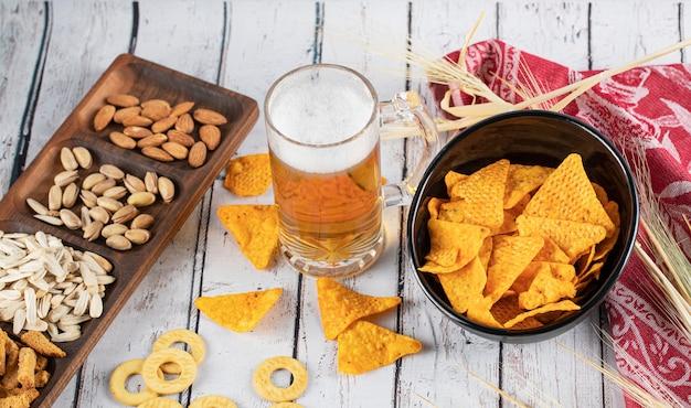 Чипсы, пиво и сухофрукты на столе Бесплатные Фотографии