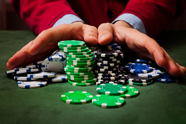 Chips in the foreground, in the blurring of the hands of a man holding chips , playing poker Premium Photo
