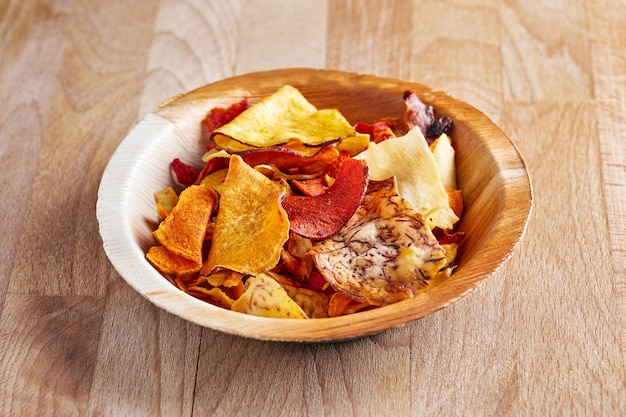 天然物、ビート、ジャガイモ、ニンジン、サツマイモのチップスを木の板に、木の上に。 Premium写真