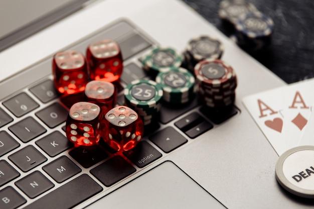 ポーカーオンラインまたはカジノギャンブルのクローズアップ用のエース付きの赤いサイコロとトランプをチップします Premium写真