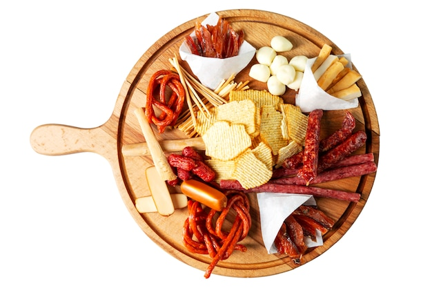 Chips, sausages and cheeses on a wooden board Premium Photo
