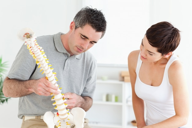Chiropractor and patient looking at a model of a spine Premium Photo