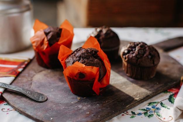 チョコブラウニー甘いおいしいおいしい丸いものは、昼間の茶色の木製の机の上のチョコバイトで設計されました 無料写真
