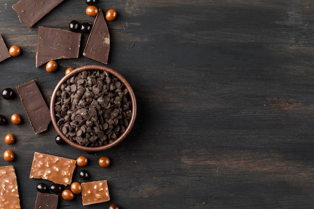 Choco drops with chocoballs and choco bars in a clay bowl on wooden table Free Photo
