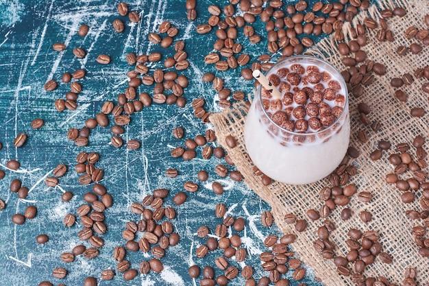Шоколад и кофейные зерна с чашкой напитка на синем. Бесплатные Фотографии