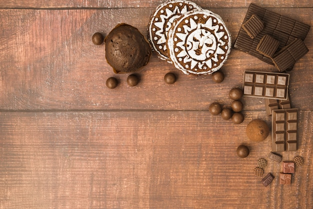 Chocolate ball; bar; muffins and baked cookies on wooden backdrop Free Photo