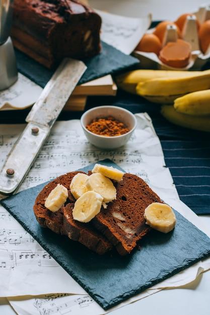 Chocolate banana bread on a black slate, with bananas Premium Photo